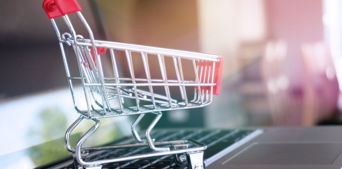 Small shopping cart with Laptop for shopping online concept.